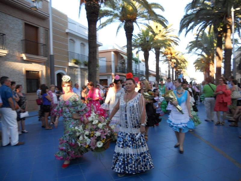 Por Las Palmeras haciendo la salida y ante la Virgen del Carmen una vez hecha la ofrenda de flores y alimentos.