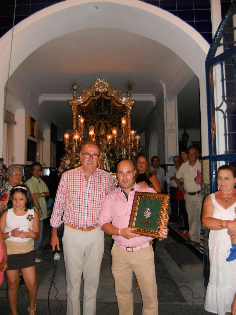 El Presidente de la Hermandad le hace entrega a David Garzón de un cuadro con la medalla