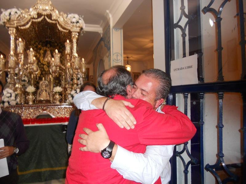 Emocionado abrazo ante el Simpecado que se dan el Presidente Francisco Amorós y el próximo Pedro Jesús Álvarez