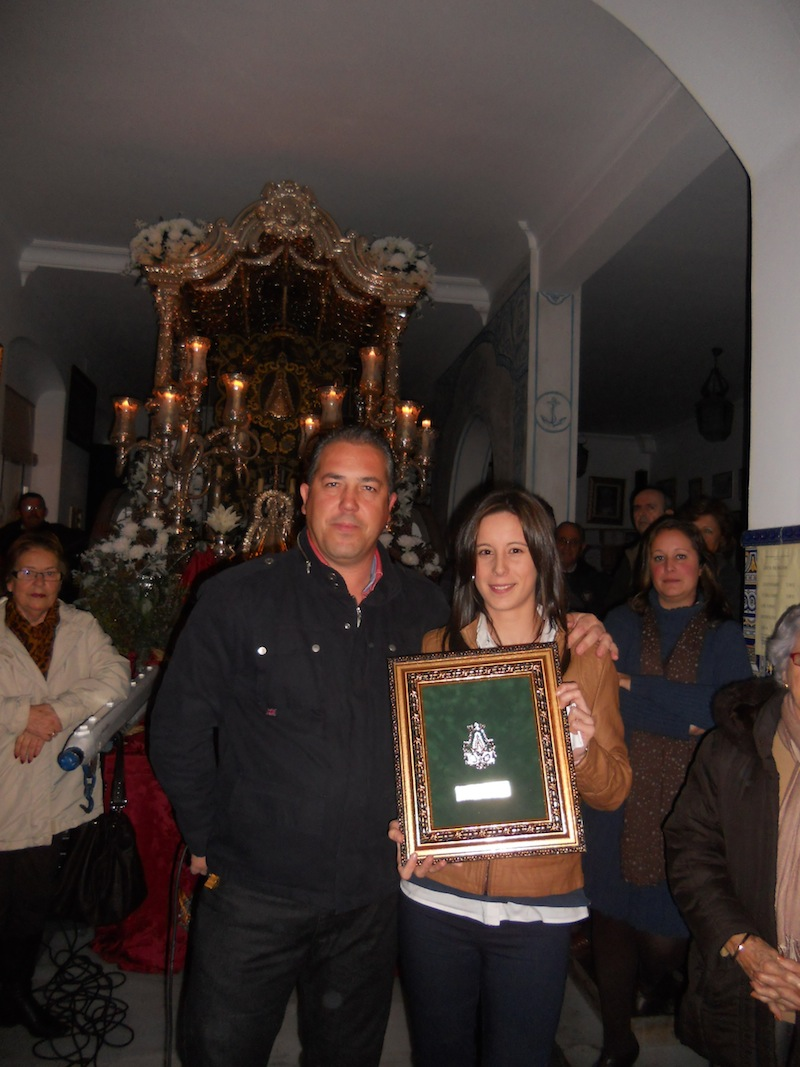 El Presidente de la Hermandad, Pedro Jesús Álvarez, entrega a Laura Reina un cuadro con la medalla de la Hermandad