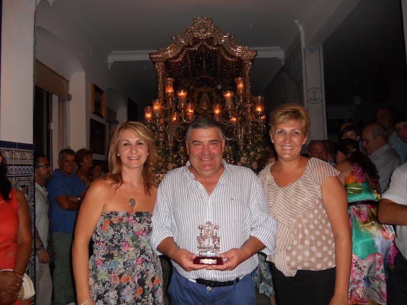 José Manuel Escobar, en nombre de la Peña La Manuela, recibe un recuerdo de manos de las Hermanas Mayores, Carmen Prieto y Sara Cáceres