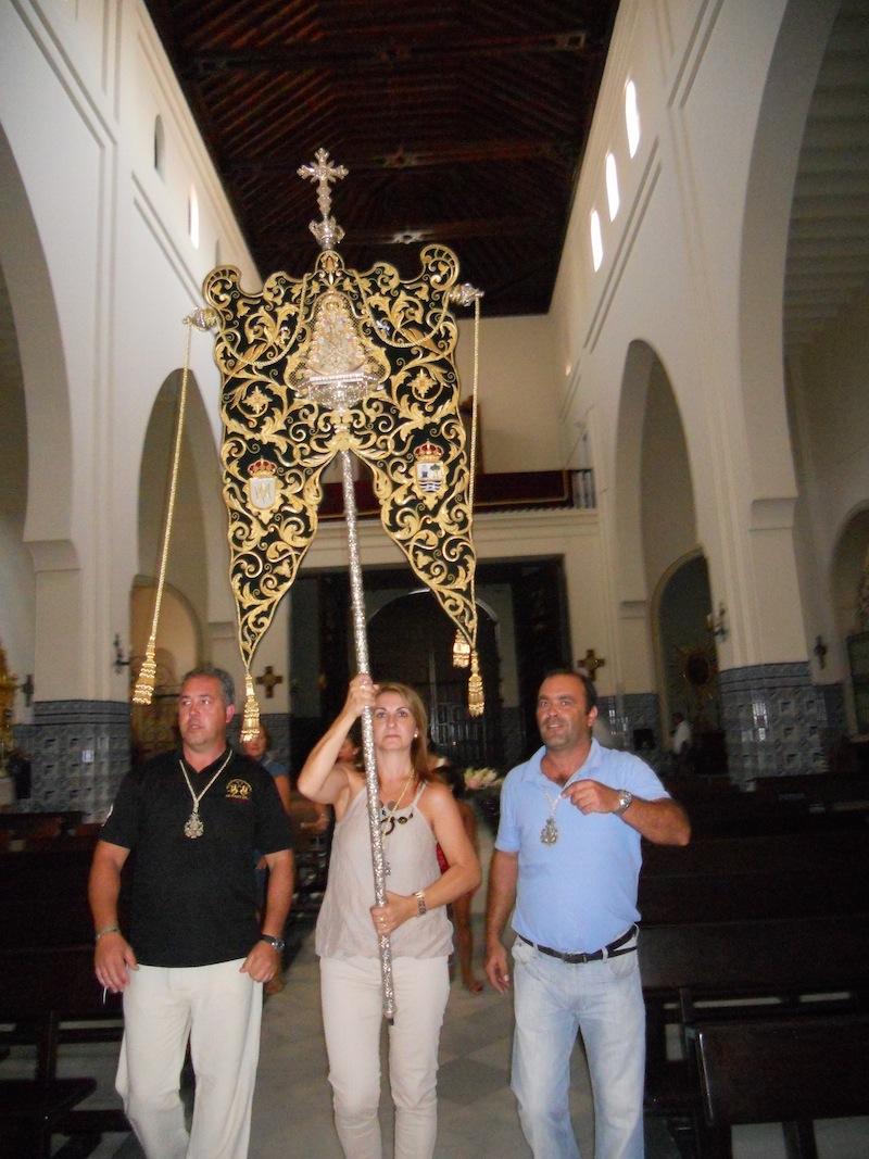 La Hermana Mayor porta el Simpecado en la Parroquia de Los Dolores hacia el Retablo