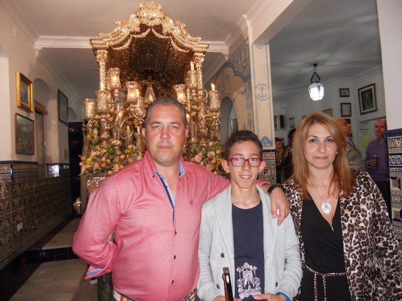 Ante la Carreta que porta el Simpecado, Antonio José Domínguez Contreras posa con la Hermana Mayor, Carmen Prieto y con el Presidente de la Hermandad, Pedro Jesús Álvarez
