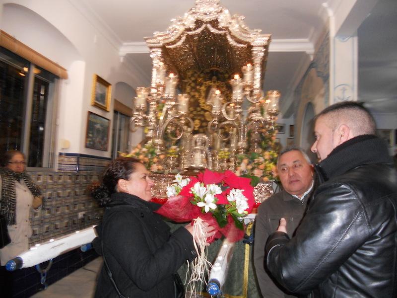 Antonio, más conocido por Cuqui, de la Peña El Soniquete, entrega a la camarista unas flores para ponerlas a los pies del Simpecado
