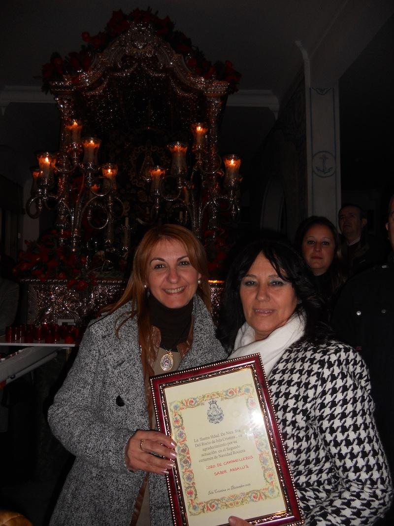 De manos de la Hermana Mayor, Carmen Prieto, Ani, en representación de Sabor Andaluz, recibe un regalo.