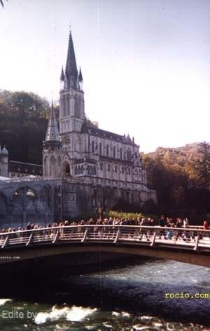 La procesión con el Simpecado de la Hdad. Matriz cruzando el río;  al fondo, bajo la Basílica, la Gruta de Massabielle