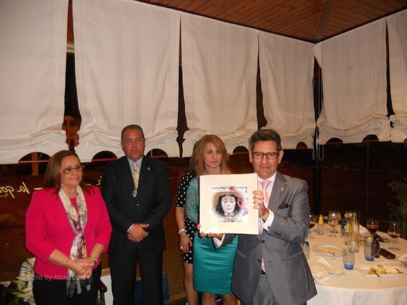 De manos de la Hermana Mayor, Rafael Salgado recibe una cerámica en la que está estampada la imagen de la Virgen de Pastora