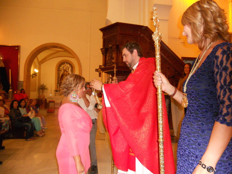 El Director Espiritual de la Hermandad impone la medalla de Hermana Mayor a Juana Rodríguez Parra