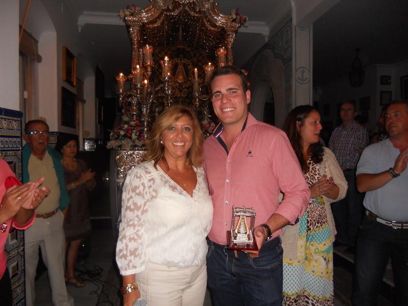 La Hermana Mayor, Juana Rodríguez, entrega un regalo a Abrahán en representación de Los Tomilleros