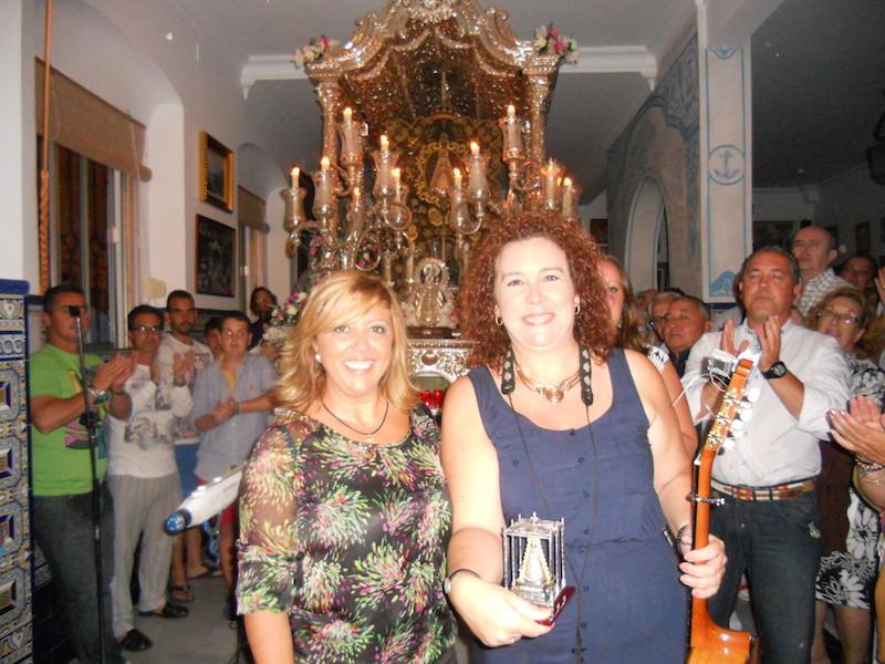 Mª Toni Contreras, en nombre de La Familia, recibe de manos de la Hermana Mayor, Juana Rodríguez, la imagen de la Virgen del Rocío en su Paso