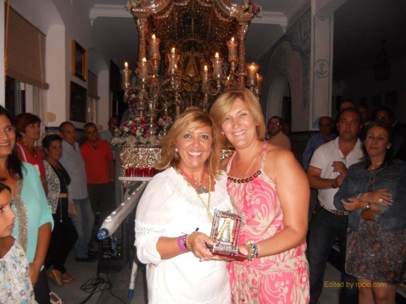 De manos de la Hermana Mayor, Juana Rodríguez, Sara Cáceres recibe un réplica del Paso de la Virgen del Rocío
