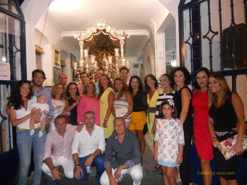 Foto de familia en la que la mayoría de los miembros de la Casa Tintineo están con la Hermana Mayor ante la Carreta del Simpecado