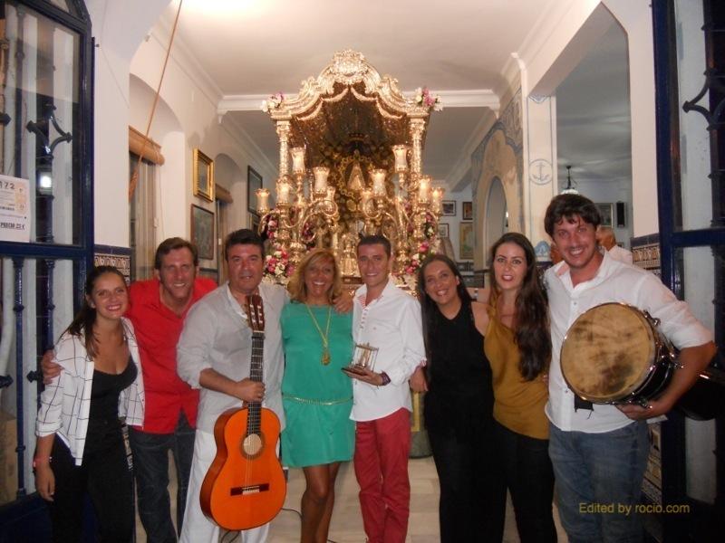 Nacho Vinagre, Joaquín Pandolfo y sus amigos acompañan a la Hermana Mayor, Juana Rodríguez, en esta foto de familia ante la Carreta del Simpecado