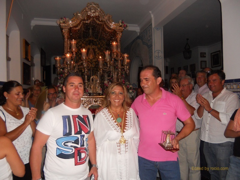 Diego, de Kalandraque, y Ramón, de Siempre Contigo, reciben de la Hermana Mayor, Juana Rodríguez, un recuerdo de la Hermandad