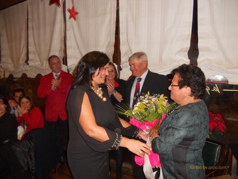 La mujer de Alfonso, Catalina Rodríguez, recibe de su hija Rocío, Tesorera de la Hermandad, un ramo de flores