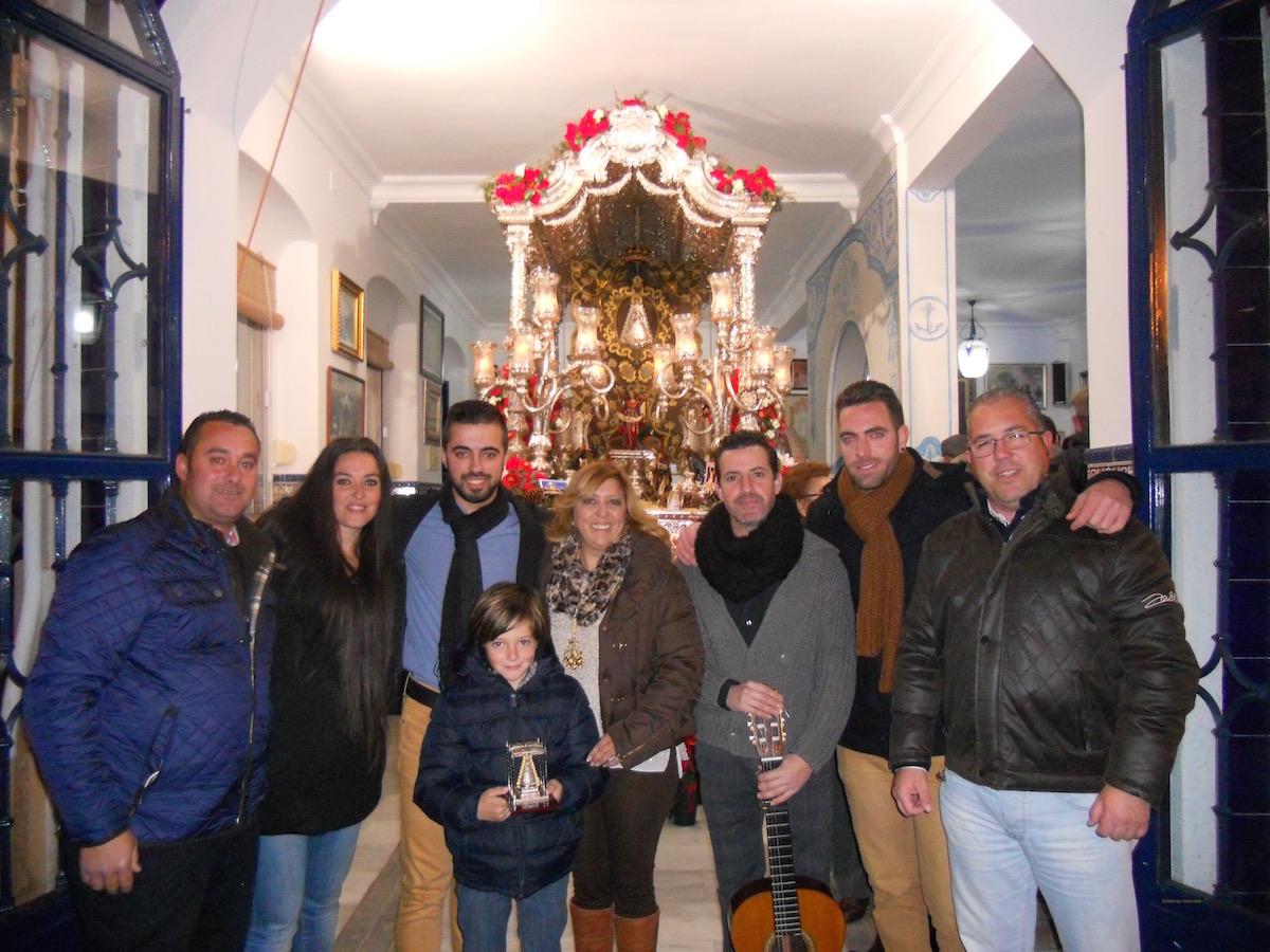 """Foto de familia ante el Simpecado del grupo """"Los que te rezan cantando"""" junto a la Hermana Mayor y al Presidente de la Hermandad, Pedro Jesús Álvarez."""