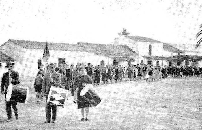 Los peregrinos de Triana en correcta formación se dirigen desde su casa de la Aldea al Santuario para oír la Santa Misa del 1 de noviembre de 1959. Foto C. Milla (Revista Rocío No14)