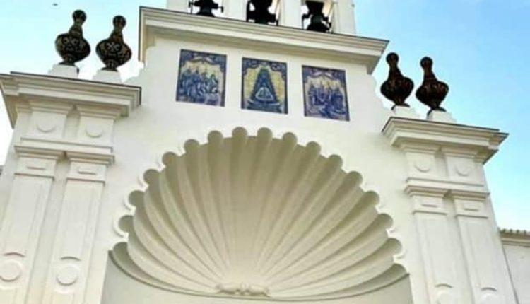 La puerta del Santuario adornada con una foto de la Virgen del Rocío y las medallas de las filiales